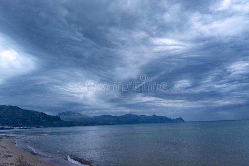 Scenic gray-blue clouds during sunrise over coastline with sandy beach and clear sea water in Alcamo Marina, small town in Sicily. Scenic gray-blue clouds during stock image