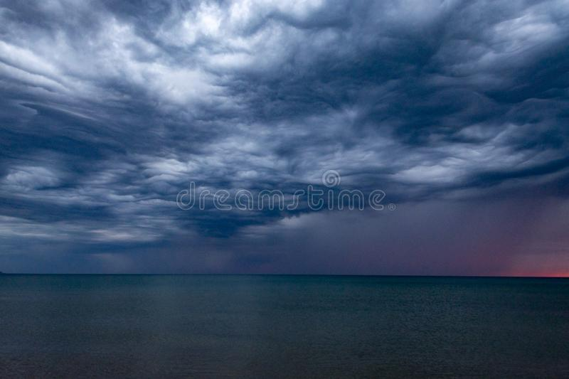 Scenic gray-blue clouds during sunrise over coastline with sandy beach and clear sea water in Alcamo Marina, small town in Sicily. Scenic gray-blue clouds during royalty free stock photos