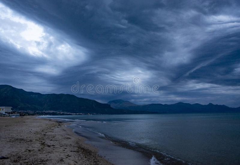 Scenic gray-blue clouds during sunrise over coastline with sandy beach and clear sea water in Alcamo Marina, small town in Sicily. Scenic gray-blue clouds during royalty free stock photography