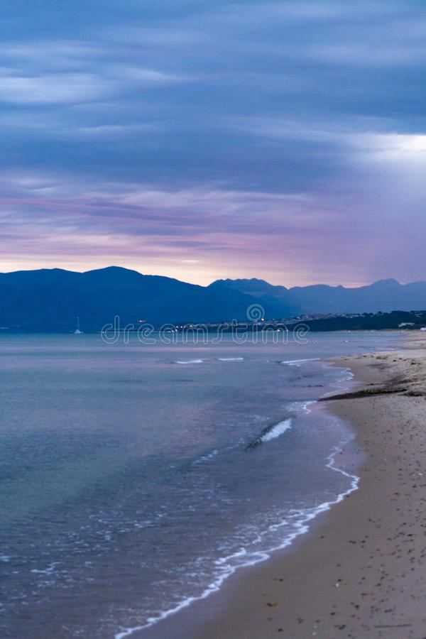 Scenic gray-blue clouds during sunrise over coastline with sandy beach and clear sea water in Alcamo Marina, small town in Sicily. Scenic gray-blue clouds during royalty free stock image