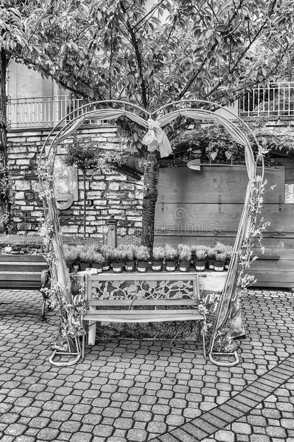 Scenic heart-shaped bench decorated with flowers and laces royalty free stock images