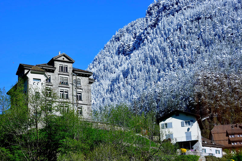 Scenic house in snowy mountain Alps royalty free stock image