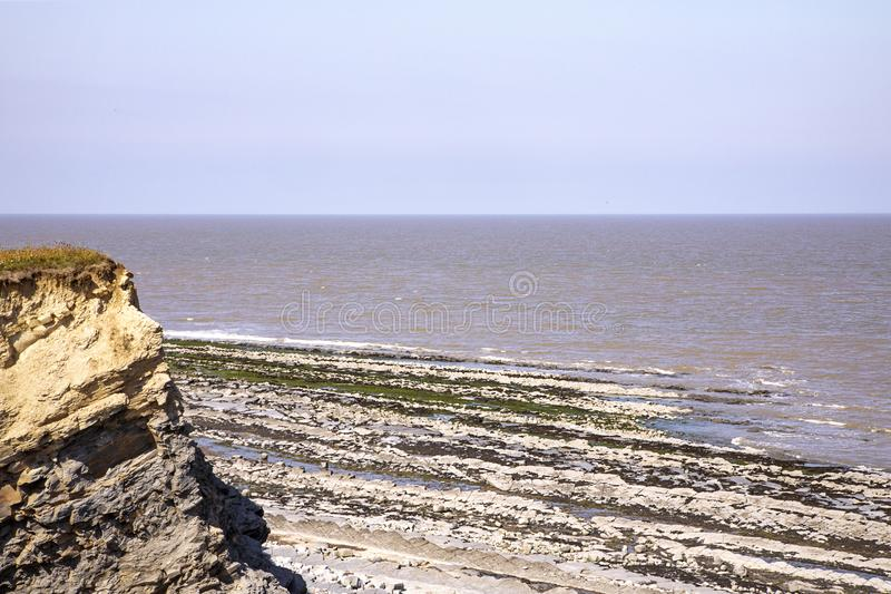 Scenic Kilve beach Somerset England. Summer day. English coast landscape. Horizon line, sunny day. UK. Scenic english beach landscape with cliff. Interesting royalty free stock image