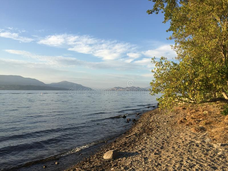 Scenic lake landscape view with rocky beach and waves on shoreline. royalty free stock photos