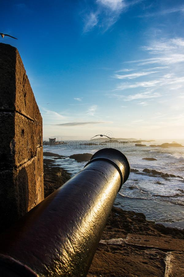 Scenic landscape of Atlantic ocean at sunset with old metal cannon in the foreground. Essaouira, Morocco stock images