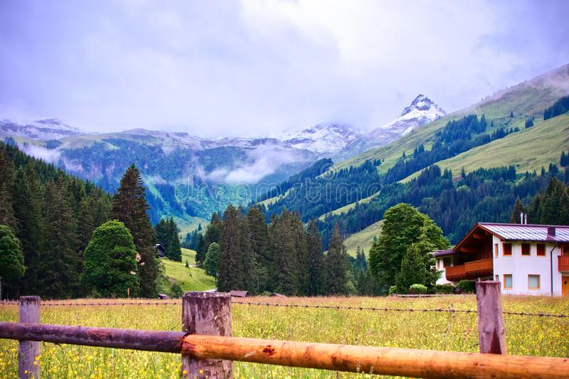 Alpine mountain with a snowy peak with a wood fence and chalets in the foreground at Talschlu� in Saalbach, Austria stock photography