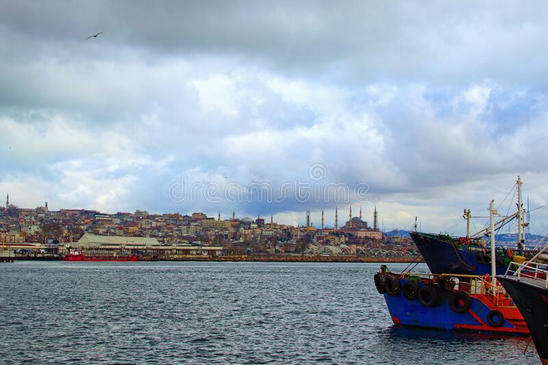 Scenic landscape of harbor with moored fishing boats and ships in Istanbul. Cityscape in the background. Dramatic winter sky. Istanbul, Turkey royalty free stock image