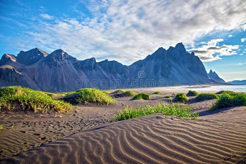 Scenic landscape with most breathtaking mountains Vestrahorn on the Stokksnes peninsula and cozy lagoon with green grass on the. Sand dunes in Iceland. Exotic stock photos
