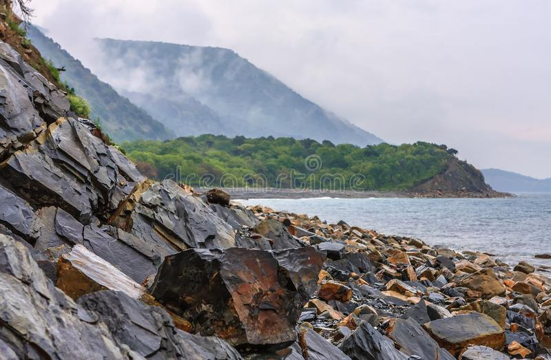Scenic landscape of rocky Black sea coast by Anapa on green Caucasus mountain forest background royalty free stock images