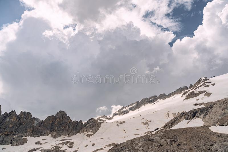 Scenic landscape with rocky mountain under cloud sky. Scenery landscape with high rocky mountain under cloud sky in Alps. Copy space in left side stock image