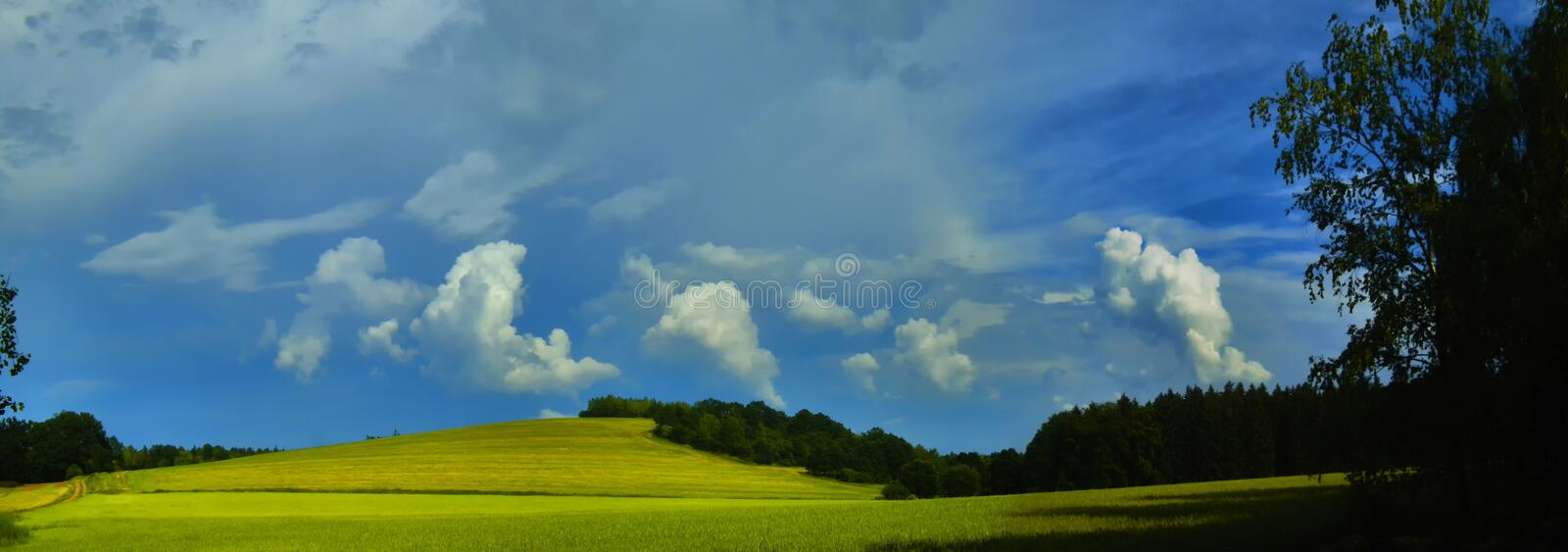 Scenic landscape with storm cloud in background over green agriculture fields. Tree and meadows at spring daylight. Dramatic storm clouds and sky.Relaxing royalty free stock images