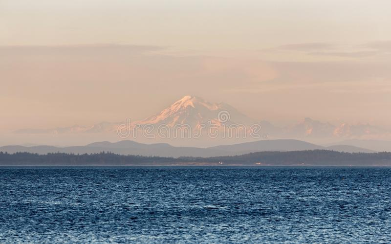 Mount Baker Sunset Landscape View from Oak Bay, Victoria BC Canada. Scenic Landscape View of Distant Mount Baker near Seattle, Washington USA seen through haze stock image
