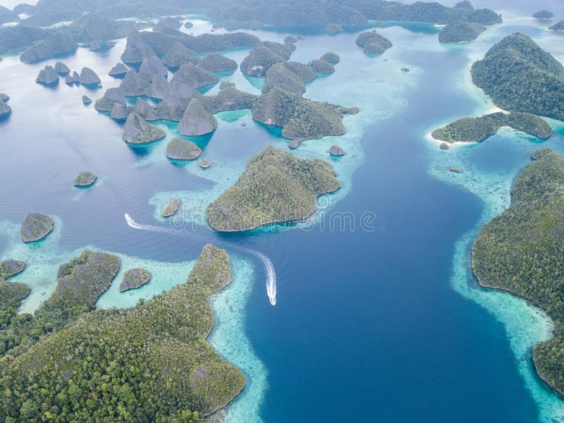 Aerial View of Scenic Islands in Raja Ampat. The scenic limestone islands in Wayag, Raja Ampat, are surrounded by healthy, shallow coral reefs. This remote royalty free stock photo