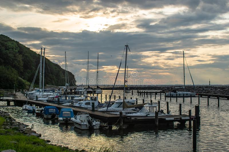 Scenic little harbour with sailing boats at sunset light stock image