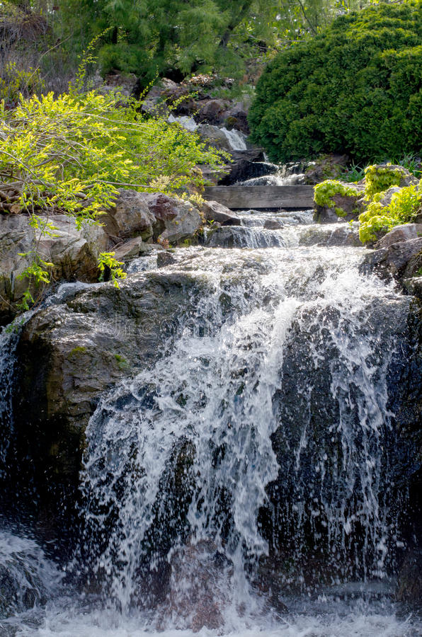 Scenic man made waterfall in a garden stock images