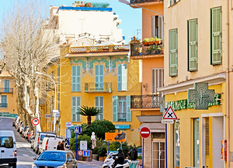 The scenic mansion. MENTON, FRANCE - FEBRUARY 22, 2012: The scenic mansion with the corner facade, decorated with colorful traceries, located in the busy street royalty free stock photography