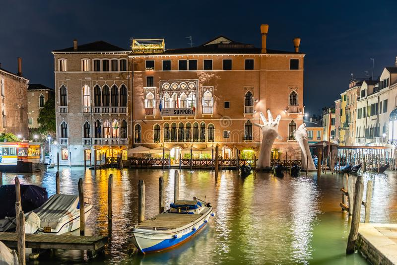 Scenic monumental sculpture in the Grand Canal of Venice, Italy. VENICE, ITALY - APRIL 29: View at night of the scenic monumental sculpture of a child's royalty free stock photo