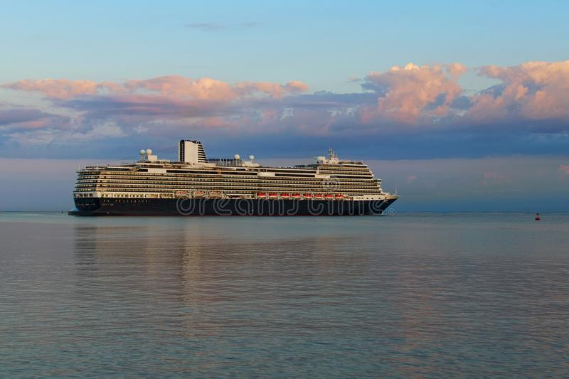 Scenic morning view of huge luxury cruise ship on the horizon. It glides to the port of Koper during magic sunrise royalty free stock images