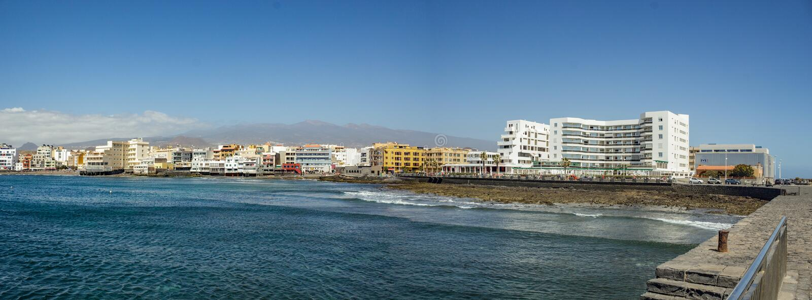 Scenic morning vistas towards El Medano village from the pier with the picturesque buildings and small beach in front, and stock photography