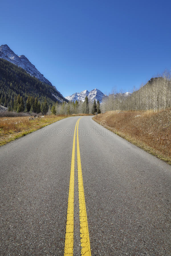 Scenic mountain road, Maroon Bells in distance. royalty free stock image