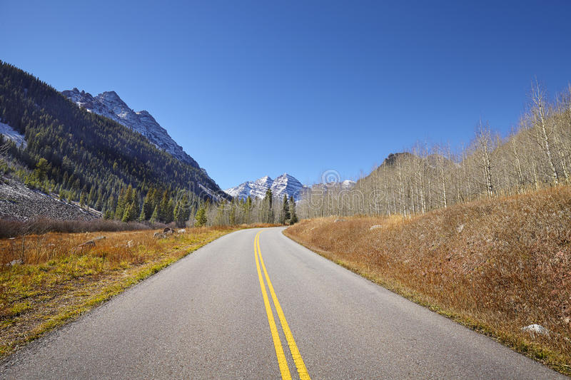 Scenic mountain road, Maroon Bells in distance. royalty free stock photo
