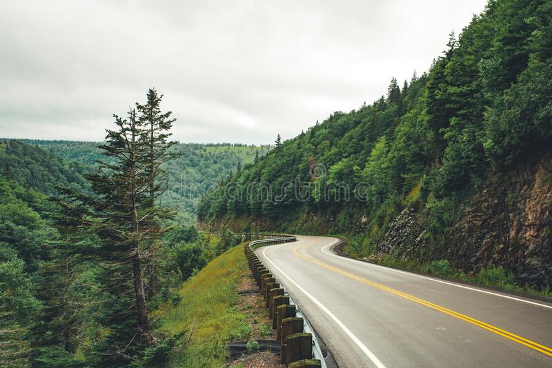 Scenic mountain winding road after the rain. Wet road and steep hills. Scenic mountain winding road after the rain. Green forest steep hills in the background stock image