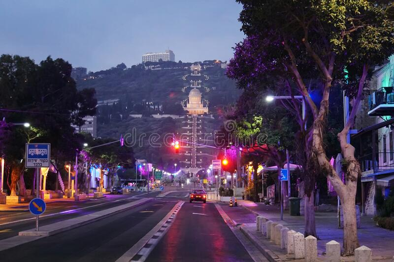 Scenic night view of the bahai temple and bahai gardens from the central street in Haifa, Israel. Deserted night road. And red traffic light at background of royalty free stock image