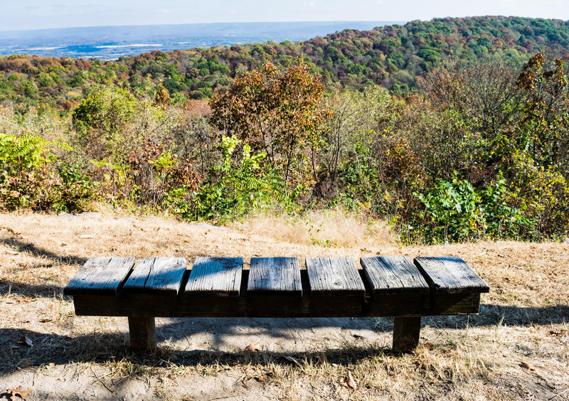 Scenic overlook, trees, mountains, solitary park bench. Wood slat park bench at scenic overlook, Monte Sano State Park, Alabama, USA. Trees on mountains are royalty free stock photography
