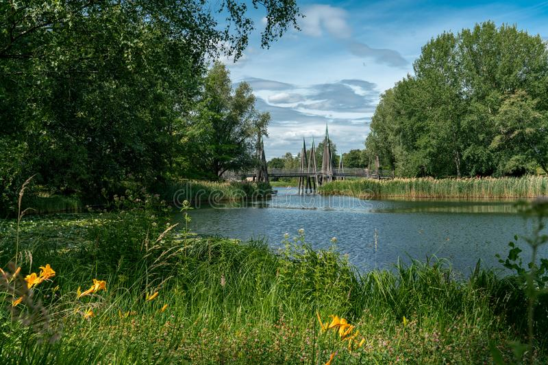 Scenic panorama of a lake with reeds and plants crossed by a wooden bridge. Scenic panorama of a lake with reeds and plants at the borders and crossed by an stock photo