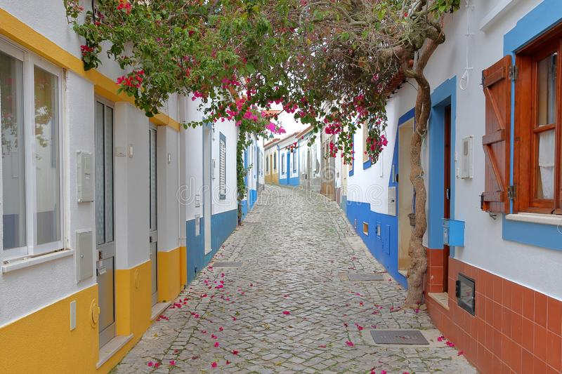 A scenic paved alley with colorful houses and flowers in the fishing village of Ferragudo, Algarve stock photo