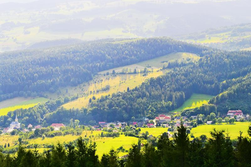 Scenic picturesque countryside landscape. Vast panorama view of Jugow village in the Owl Mountains Gory Sowie, Poland. Misty rural scenery aerial view stock photo