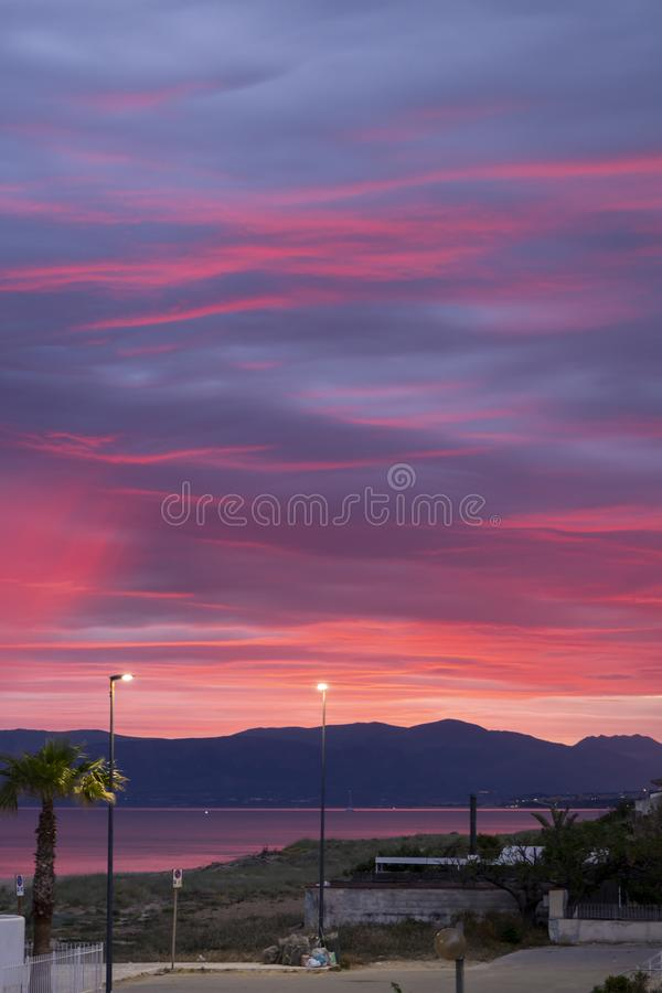 Scenic red sunrise over coastline with sandy beach and clear sea water in Alcamo Marina, small town in Sicily, Italy, summer. Scenic pink-red sunrise over royalty free stock photography