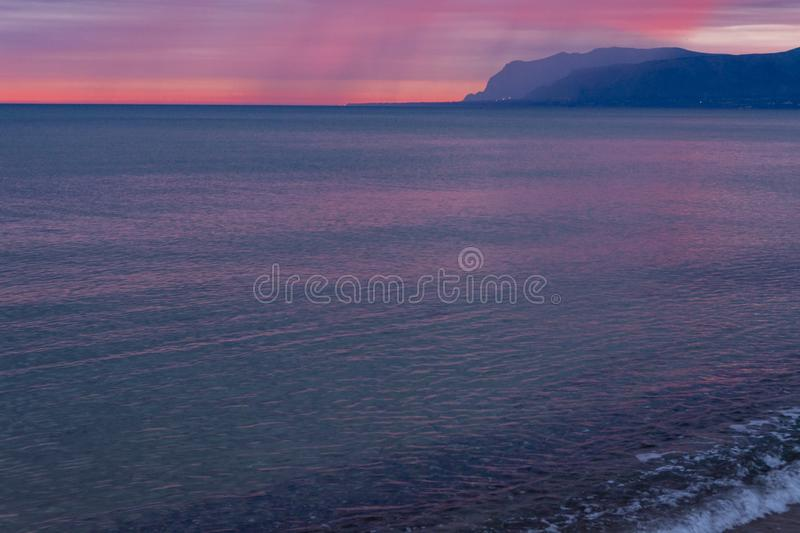 Scenic red sunrise over coastline with sandy beach and clear sea water in Alcamo Marina, small town in Sicily, Italy, summer. Scenic pink-red sunrise over royalty free stock images