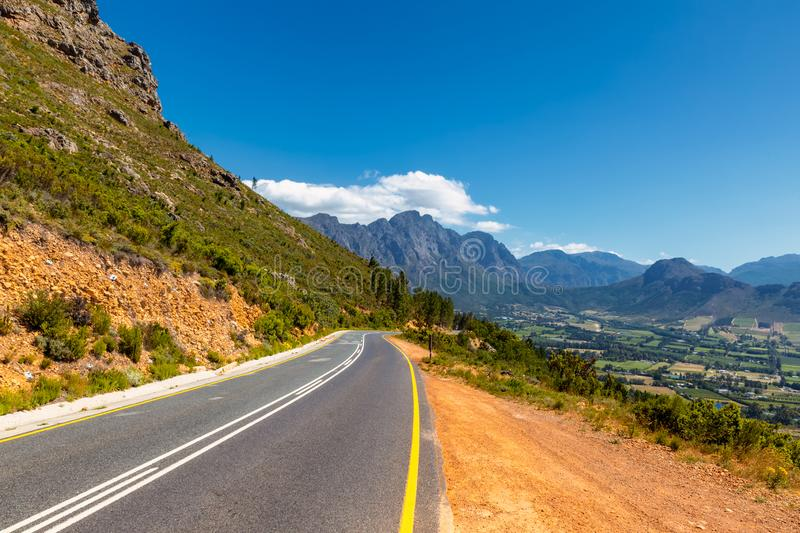 Scenic road at Franschhoek valley with its famous wineries and surrounding mountains royalty free stock image