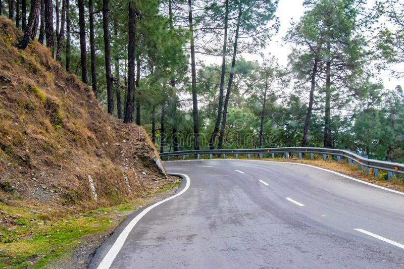 Scenic road through the valley of banikhet dalhousie himachal pradesh covered with mountain and trees. Driving uphill scenic road royalty free stock photography