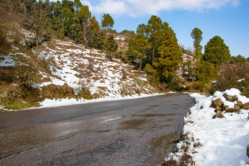 Scenic road through the valley of banikhet dalhousie himachal pradesh. Covered with Snow mountain and trees. Driving uphill scenic road winter travel concept stock photography