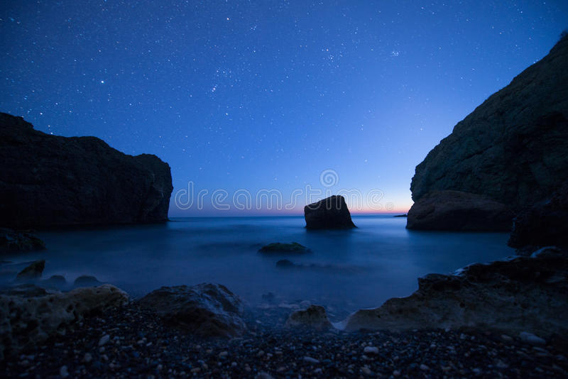 Scenic rocky seashore at sunset under the stars. Stones in the sea on a long exposure stock images