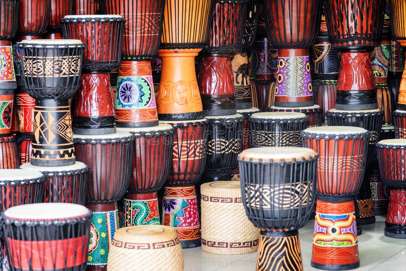 Scenic rows of colorful wooden djembe drums at souvenir shop. Fenghuang, China - September 22, 2017: Scenic rows of colorful wooden djembe drums at souvenir shop stock photography