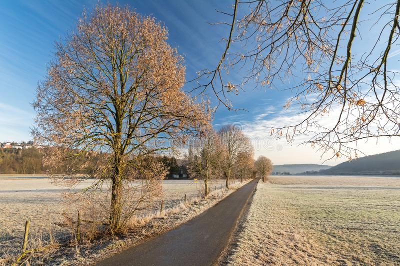 Scenic rural autumn landscape with foot path and fields covered with frost stock image