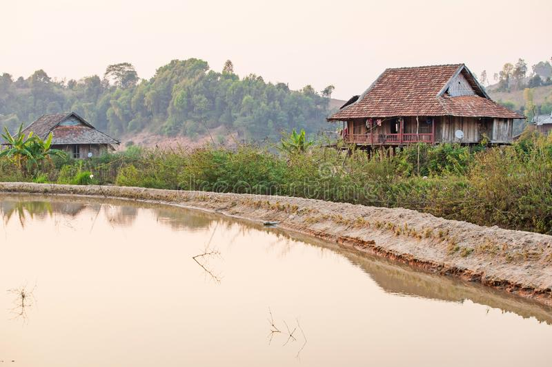 Scenic rural of vietnam at sunset, two old wooden house, brown earthenware roof, pool foreground, forest and mountains backgrounds royalty free stock images