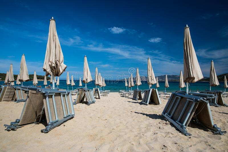 Scenic Sardinia island landscape. Italy sea coast with azure clear water. Beach with umbrellas and loungers ready for the royalty free stock photos