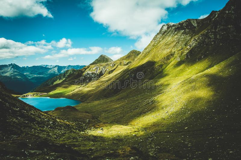 Scenic shot of green mountains near a lake at daytime under the beautiful cloudy sky. A scenic shot of green mountains near a lake at daytime under the beautiful stock images