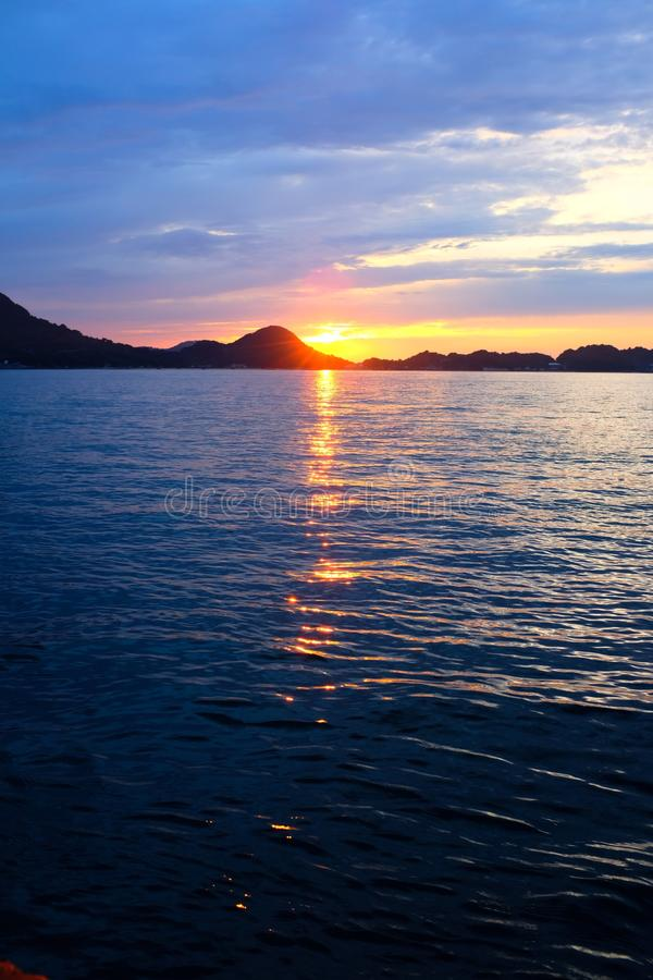 Scenic shot of  the sunset reflected in the ocean under the beautiful cloudy sky royalty free stock image