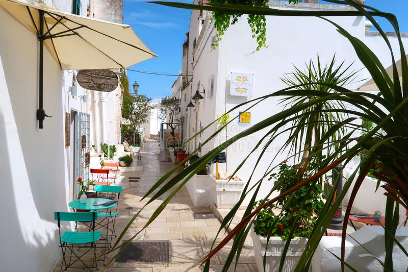 Scenic sight of the Ostuni town sunny street with typical restaurants and blooming flowers, Apulia region, Italy, Adriatic Sea stock photography