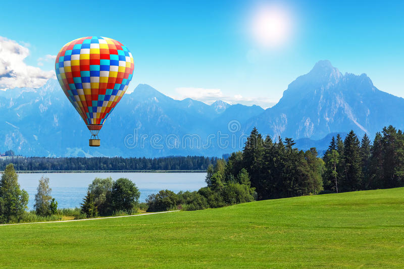 Scenic summer landscape with hot air balloon, lake and mountains royalty free stock photos