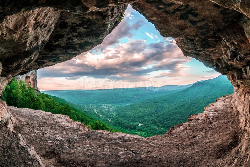 Scenic summer landscape view of Mezmay village from inside weird rocky grotto in Caucasus mountains, Lenina Rock shelf, Russia stock photo