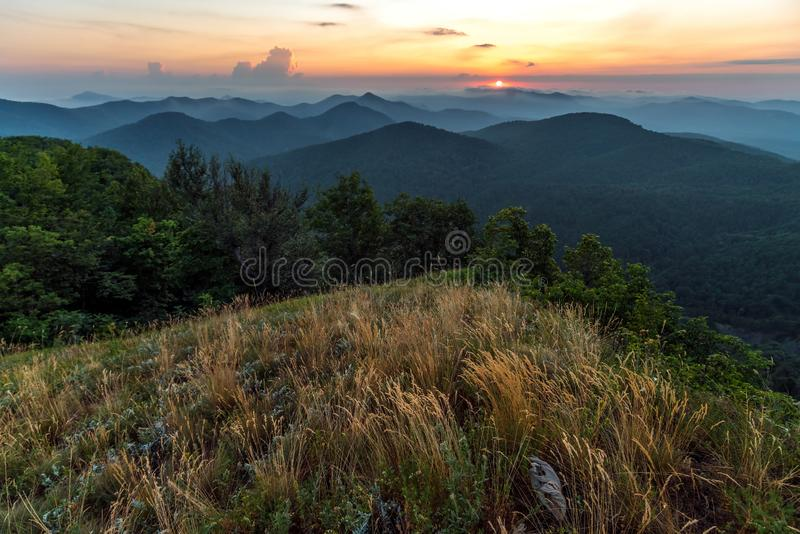 Scenic summer sunset in hazy Caucasus mountains. Sun setting bihind clouds. Beautiful landscape from top of Lysaya mountain in stock photos