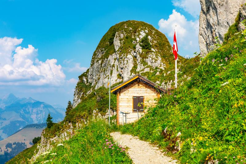 Small wooden house in Alps Mountains, Switzerland. Scenic summer view of small wooden house, home or cottage and Swiss state national flag in Rochers de Naye royalty free stock photography