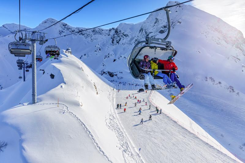 Scenic sunny winter landscape of skiers and boarders riding on ski track and chair ski lift at Gorky Gorod mountain ski resort aga. Sochi, Russia - January 7 stock image