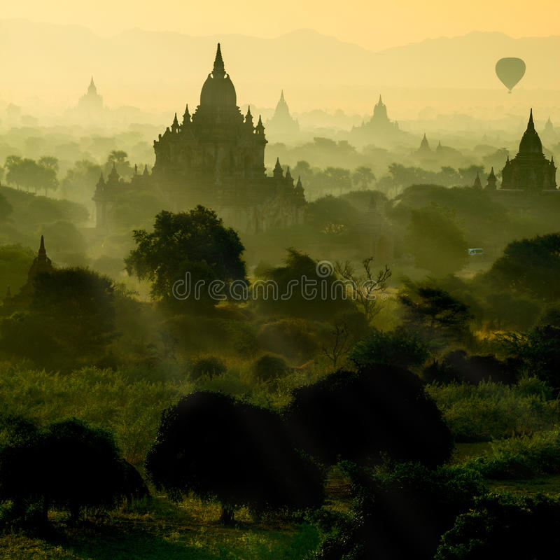 Scenic sunrise with silhouette balloons above ruin pagoda in Bagan, Myanmar. stock images